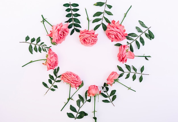 Rosas decorativas rosa dispostas em forma de coração no pano de fundo branco