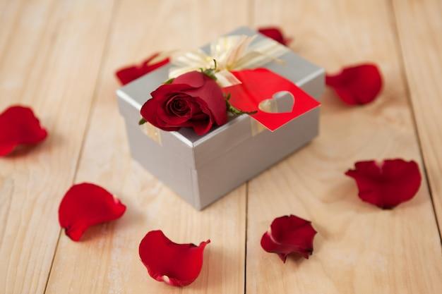 Rosas e caixa de presente cercada por pétalas de rosa