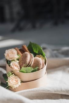 Rosas e canela com macaroons no recipiente sobre a toalha de mesa