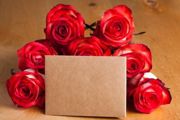 Rosas e cartão artesanal em branco sobre a mesa
