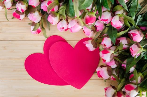 Rosas e cartão de forma de coração para sua mensagem