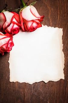 Rosas e cartão rasgado em branco sobre a mesa