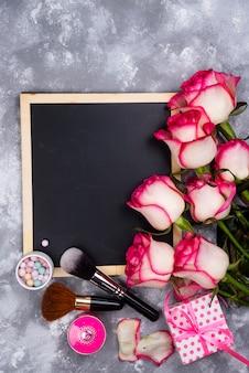 Rosas e cosméticos decorativos com uma lousa