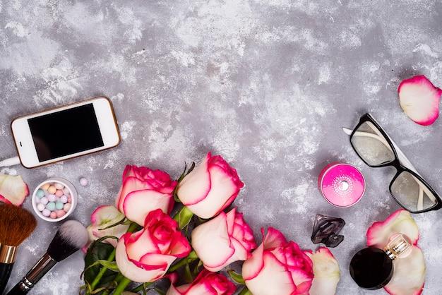 Rosas e cosméticos decorativos como moldura