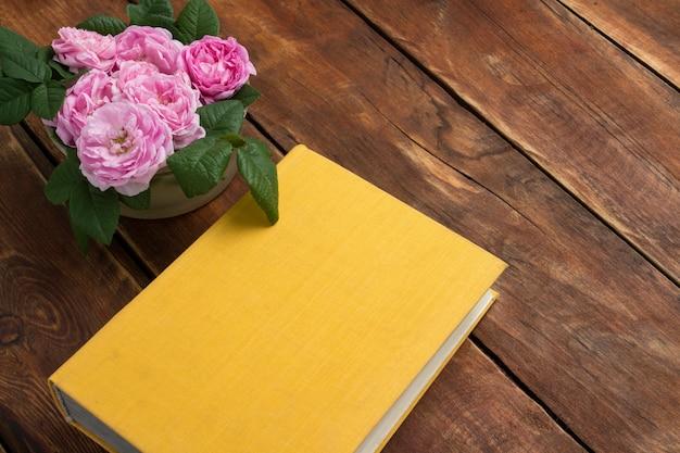 Rosas e livro com capa amarela em um fundo de madeira