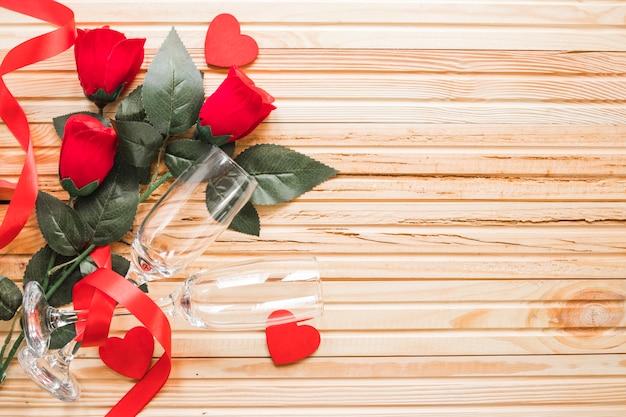 Rosas e óculos em fundo de lenha