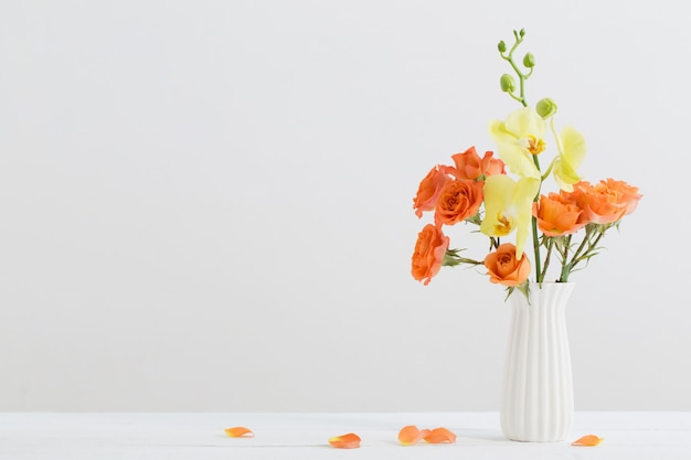 Rosas e orquídeas em vaso branco