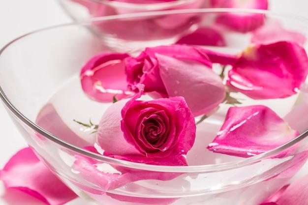 Rosas e pétalas em uma tigela com água pura. conceito de spa e bem-estar.