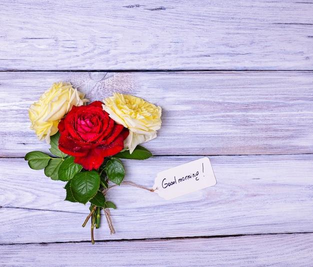 Rosas e uma etiqueta de papel com uma inscrição bom dia