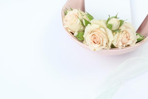 Rosas elegantes em placa rosa com cartão de convite