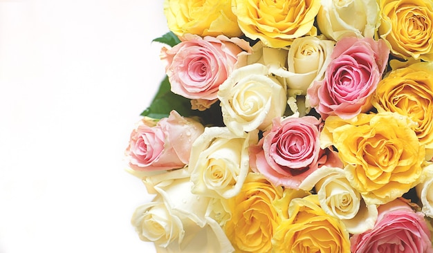 Rosas em um buquê de flores brancas, amarelas e rosa sobre um fundo claro.