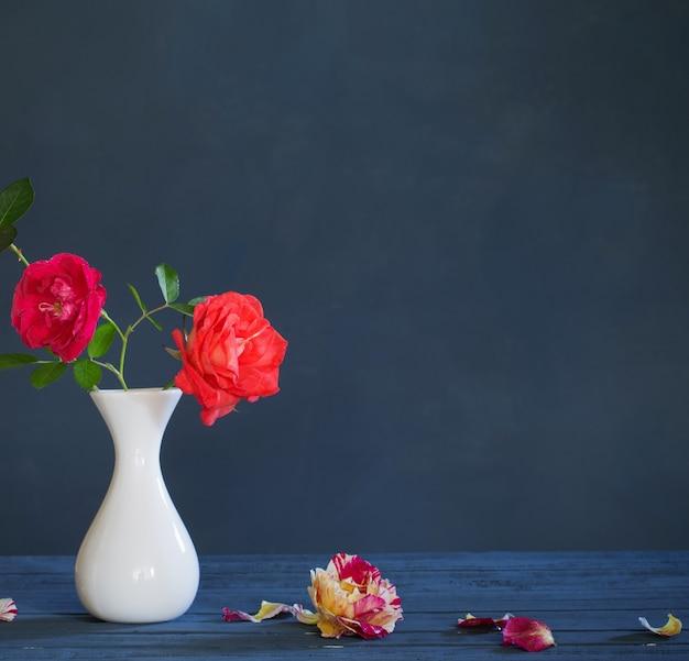 Rosas em um vaso em fundo azul escuro