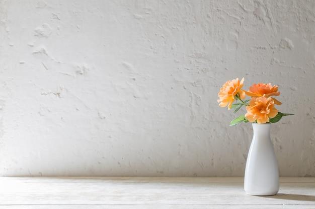 Rosas em um vaso na parede de fundo branco