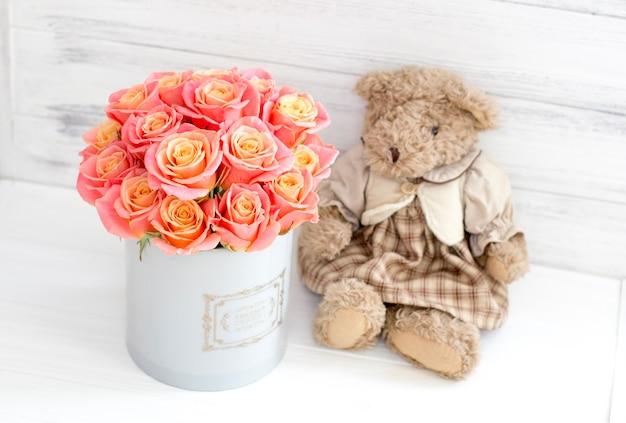 Rosas em uma caixa redonda e um urso. presente romântico. rosas em uma caixa de chapéu