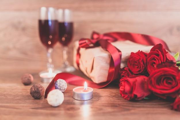 Rosas em uma mesa de madeira com um presente com um laço vermelho