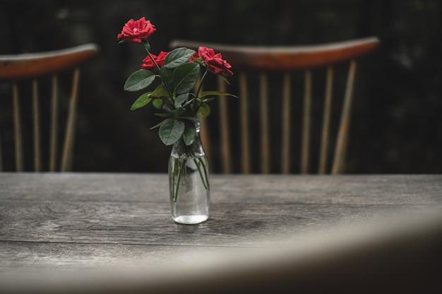 Rosas em vaso na mesa e cadeira de madeira de estilo antigo