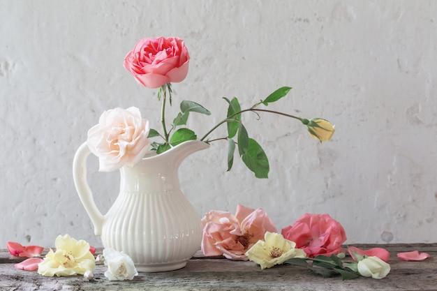 Rosas em vaso na parede branca velha