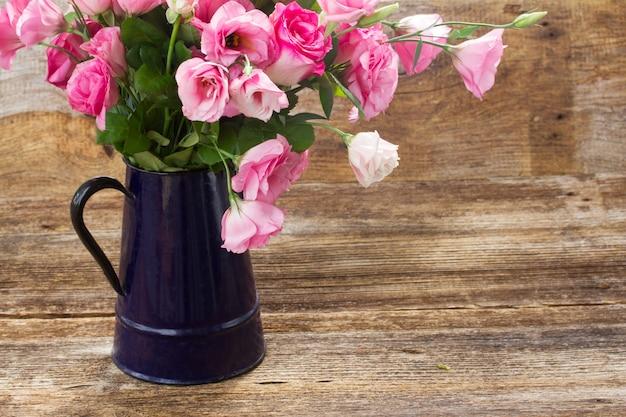 Rosas frescas e flores de eustoma em mesa de madeira envelhecida