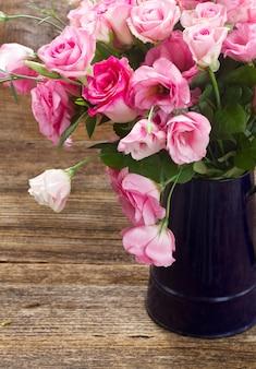 Rosas frescas e flores eustoma em vaso azul fecham na mesa de madeira