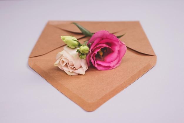 Rosas frescas em envelope de papel kraft