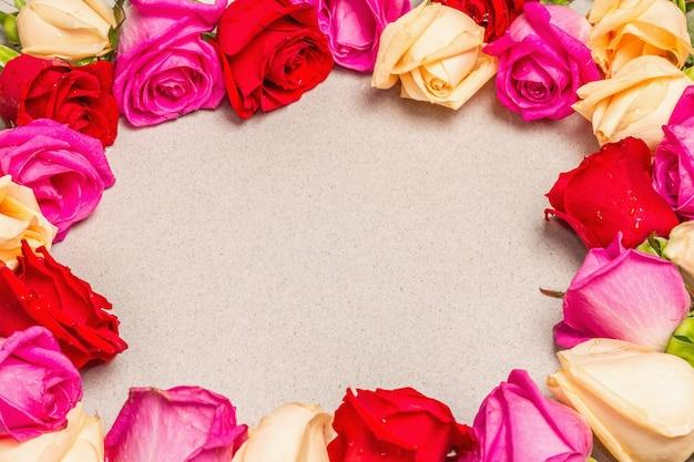 Rosas frescas multicoloridas em forma de moldura na luz de fundo de pedra. presente festivo, cartão de felicitações para a páscoa, aniversário, dia dos namorados ou casamento. conceito de férias, um lugar para texto