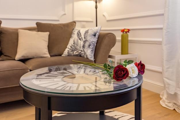 Rosas frescas na mesa de centro com relógio dentro do interior da sala de estar com sofá aconchegante