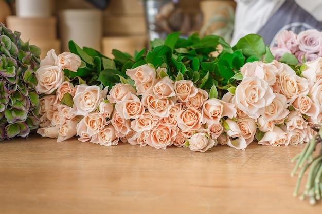 Rosas frescas para entrega de buquê. estúdio de design floral, fazendo decorações e arranjos.