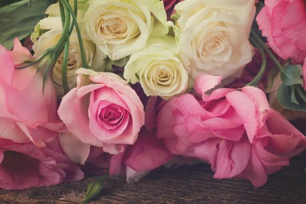Rosas frescas rosa e brancas e flores eustoma de perto, em tons retrô
