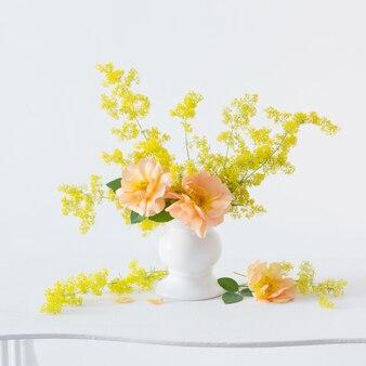 Rosas laranja com flores silvestres em buquê em um vaso branco no interior