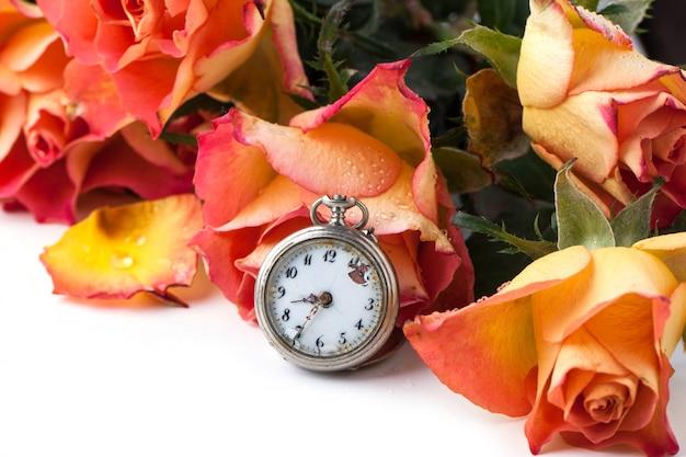 Rosas laranja com relógio vintage