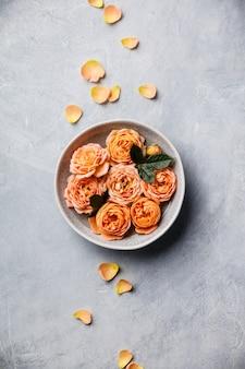 Rosas laranja flutuando na água no concreto