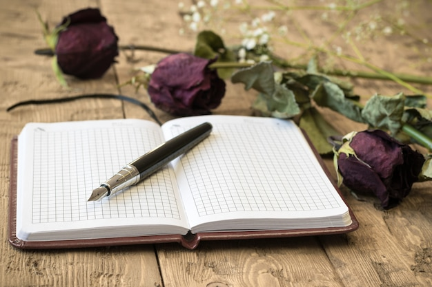 Rosas murchas com um caderno e uma caneta-tinteiro em uma mesa rústica.
