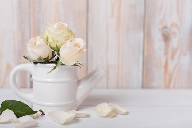 Rosas no pequeno regador de cerâmica na mesa de madeira