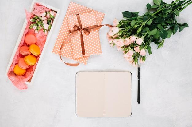 Rosas perto de caderno e presentes