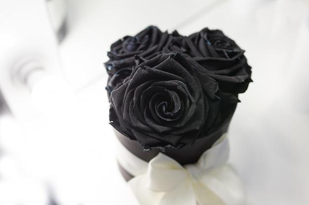 Rosas pretas em uma caixa com um laço branco sobre um fundo branco