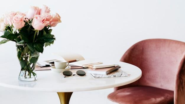 Rosas rosa claras em um modelo social de mesa branca
