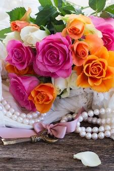 Rosas rosa e laranja com chave e pérolas
