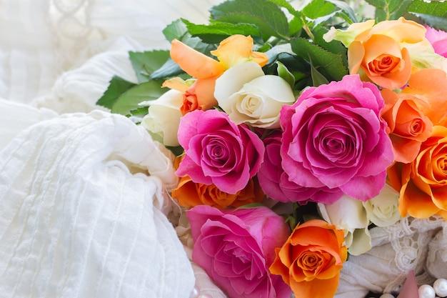 Rosas rosa e laranja em renda branca