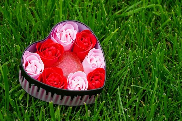 Rosas rosa e vermelhas brilhantes feitas de aparas de sabão com corações na grama verde em um vale em forma de coração ...