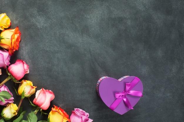 Rosas roxas e amarelas, caixa presente no fundo preto