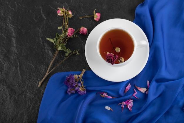 Rosas secas com uma xícara de chá quente em uma mesa preta.