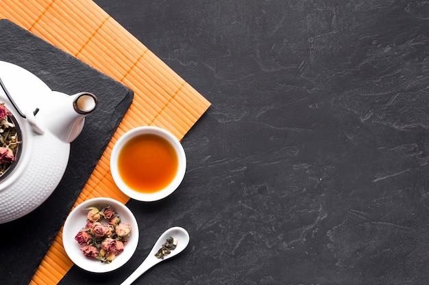 Rosas secas e chá de ervas na tigela de cerâmica na superfície preta