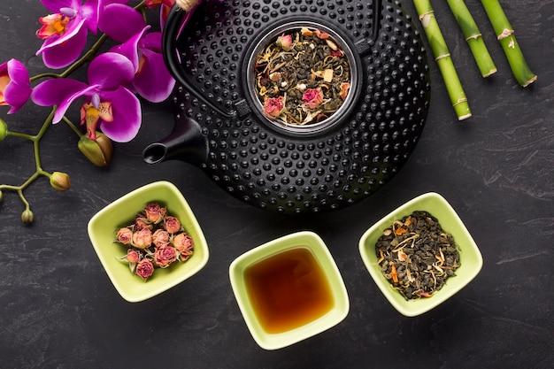 Rosas secas e ingrediente de chá de ervas com flor de orquídea em pano de fundo preto