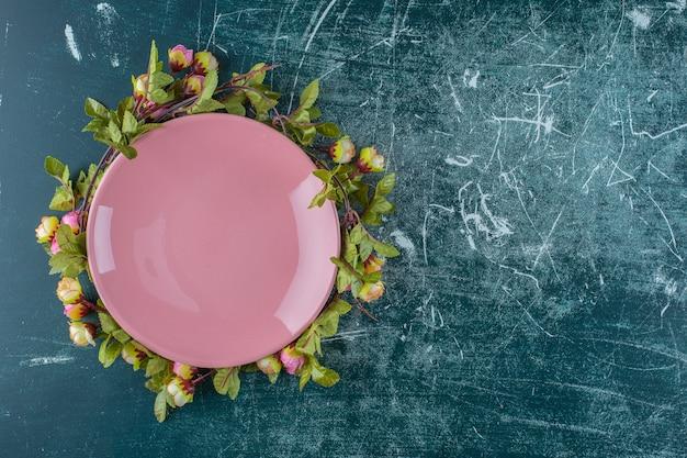 Rosas sob o prato, no fundo azul. foto de alta qualidade
