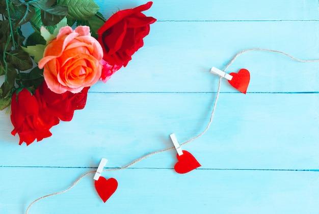 Rosas sobre fundo azul e corações apanhados por barbante. plano de fundo dia dos namorados
