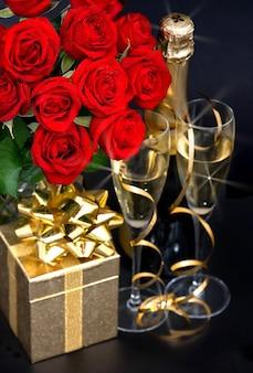 Rosas vermelhas, champanhe e um presente de ouro sobre fundo preto. decoração festiva
