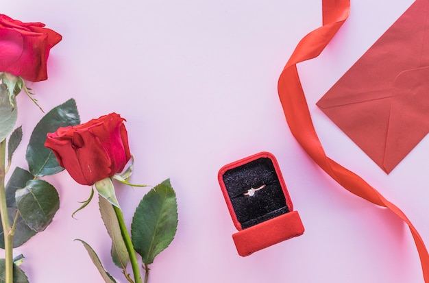 Rosas vermelhas com anel de casamento na caixa na mesa