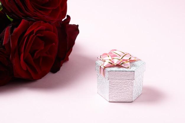 Rosas vermelhas com caixa de presente em rosa. copie o espaço. conceito de romance e amor