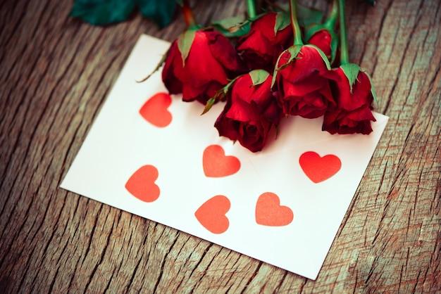 Rosas vermelhas com cartão com corações na mesa de madeira