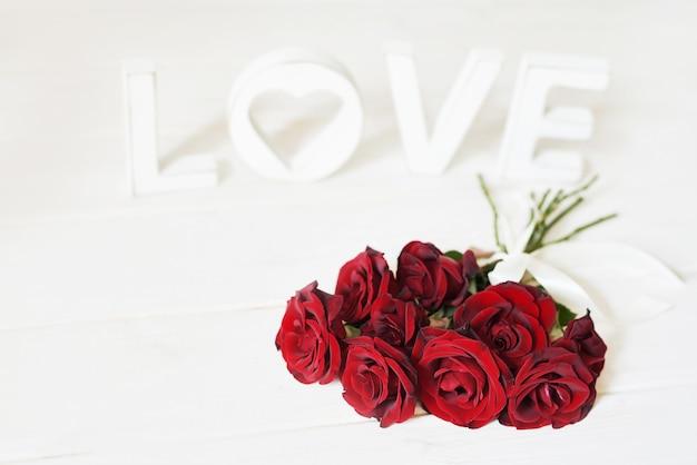 Rosas vermelhas com coração, letras de madeira amor, modelo de cartão postal